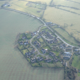 An aerial shot of Prospect Close which lies on the edge of Drayton Parslow. 2 Prospect Close is at the top left of the photo, where all the white vehicles are parked. The neighbouring field to the left directly borders the back-garden and the garage area. Notice also that 2 Prospect Close was at the head of the cul-de-sac, so neighbours would have to drive past it to access their own homes. The front-doors of the garage would have been highly visible.