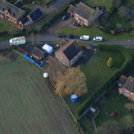 A close-up aerial shot of the garage area, facing the field. Notice the houses overlooking the front-doors of the garage.